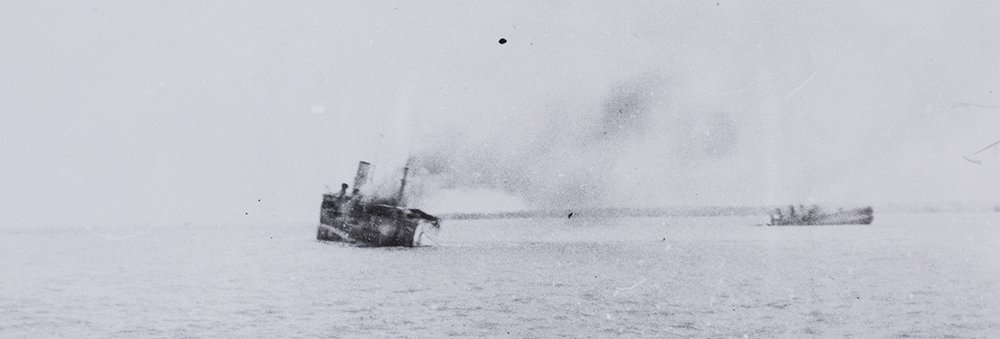 USS Peary drifting past MV British Motorist a 6,891 ton tanker which was also sunk