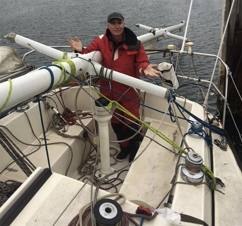Murray Stewart at the helm with the mast secured alongside at Eden. The mast is more or less is in the position it came down in and the lashings are how we did them during the night