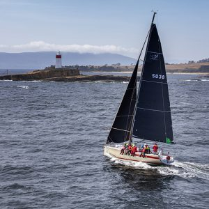 Cinquante 2019. Foreground, middle ground and background are compositional considerations in a strong image. Here we can see Mount Wellington behind the finishing line at Castray Esplanade. The Iron Pot lighthouse, a signature landmark in the race, looks tall because of the low camera angle and Cinquante skippered by Kim Jagger is powering towards the last corner at the mouth of the Derwent estuary